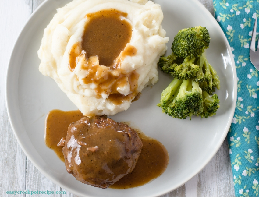 Crock Pot Salisbury Steak recipe served on a glass plate with a side of mashed potatoes and fresh brocolli