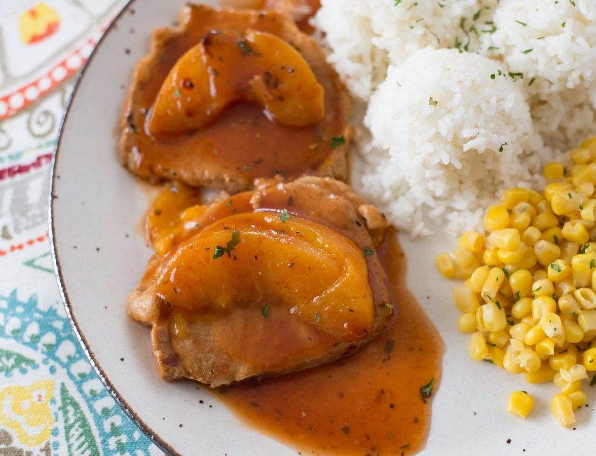 close up photo of cooked Crock Pot Spicy Peach Pork Chops with a peach slice on each chop served on a glass dinner plate with cooked white rice and corn for the perfect side dish.