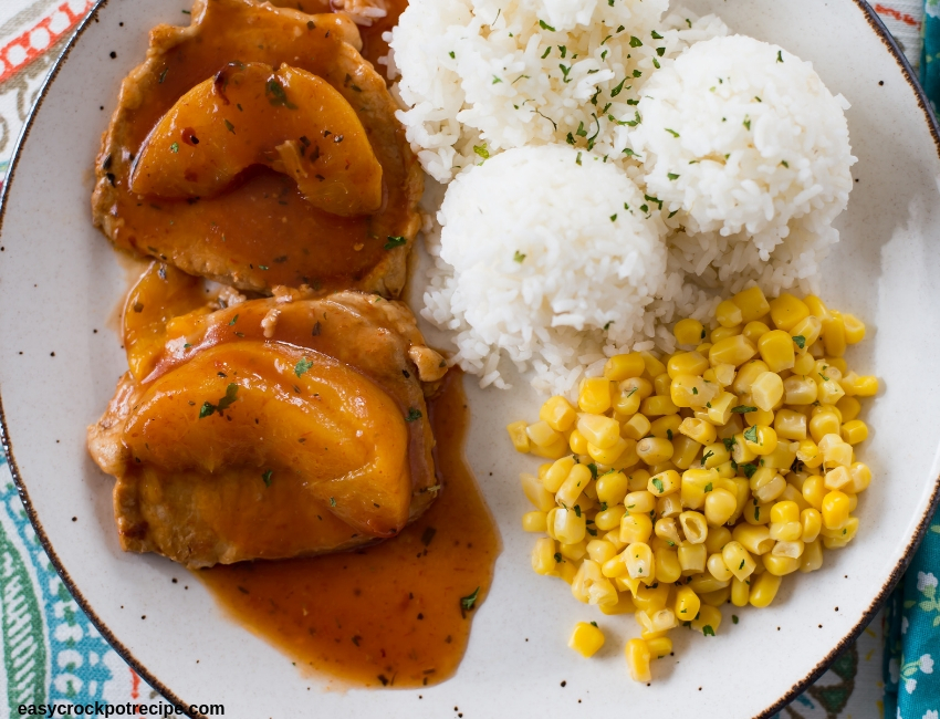 Spicy Peach Boneless Pork Chops on a glass plate served with cooked white rice and corn kernals.