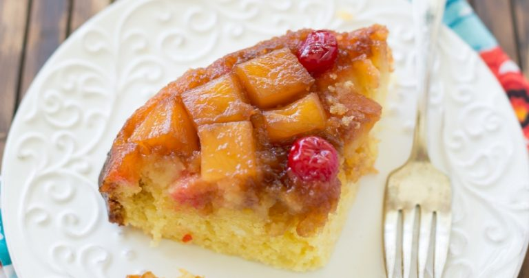 A slice of Crock Pot Pineapple Upside Down Cale on a white plate, showing the pineapple chunks and a cherry on top.